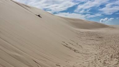 Серфинг на доске с высоких дюн