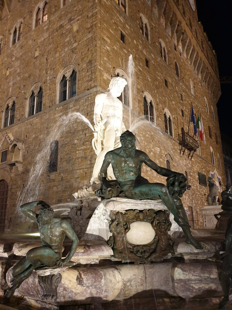 Площадь Синьории вечером с видом на Старый дворец и фонтан Нептуна.