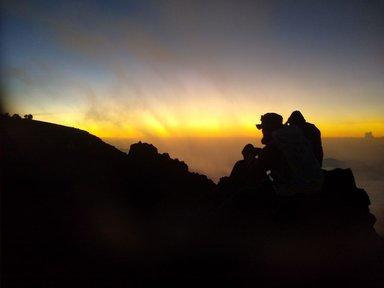 Люди сидят на уступах вершины в сумерках, и ждут солнца